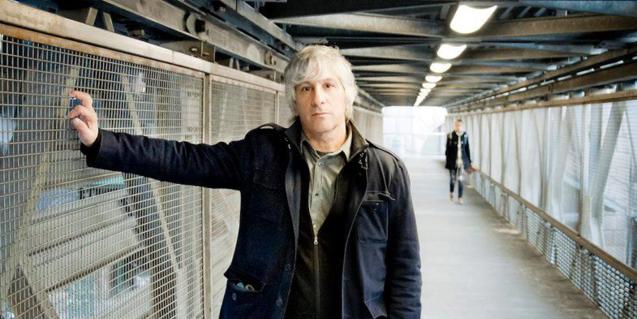 Retrat del guitarrista de rock en un pas elevat d'una ciutat indeterminada