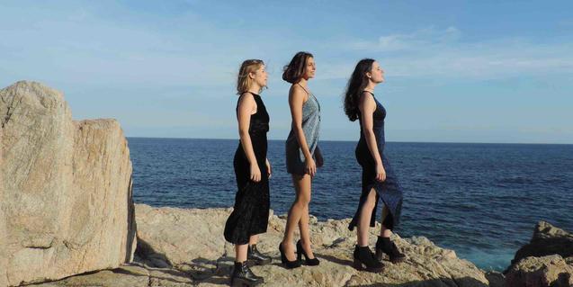 Les tres integrants de la companyia retratades dempeus davant del mar