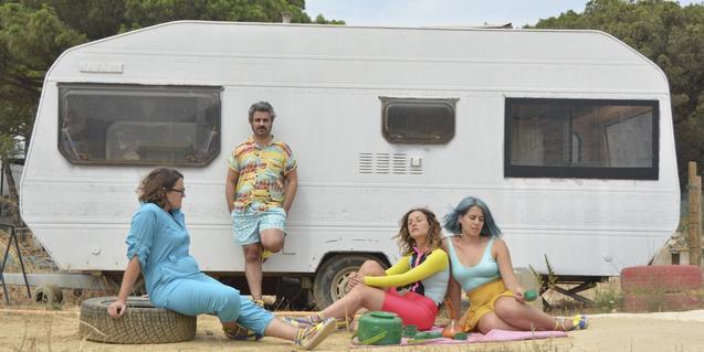 Los cuatro integrantes de la banda retratados ante una caravana