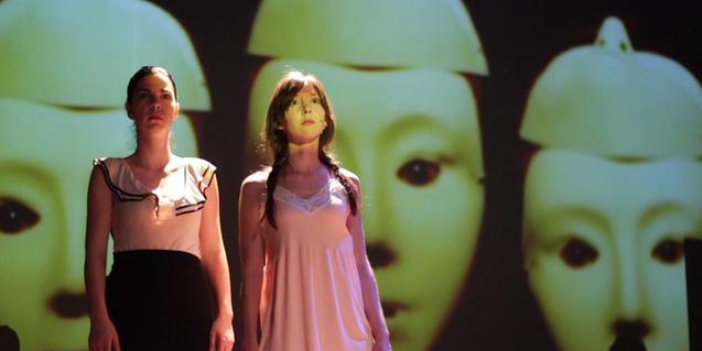 Las dos actrices protagonistas de pie sobre el escenario ante un fondo que muestra unas máscaras de gran tamaño