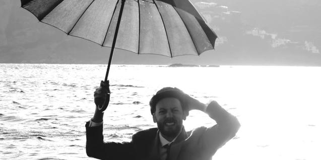 El artista, vestido y con sombrero dentro del agua de una playa conun paraguas abierto
