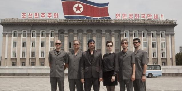 Los miembros de la banda de música Laibach haciendose una foto ante el edificio más significativo de la capital de Corea del Norte