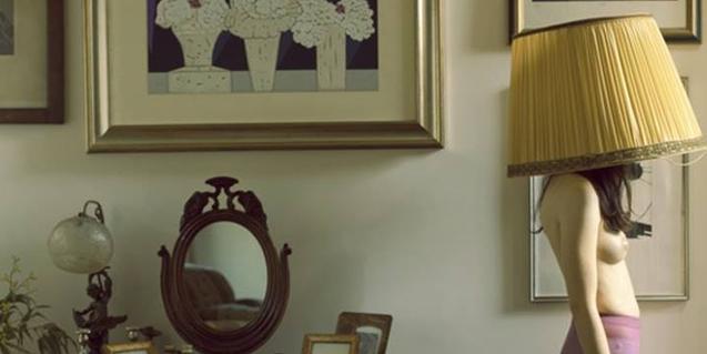 Retrato de una mujer con el pecho al descubierto y con la pantalla de una lámpara en la cabeza