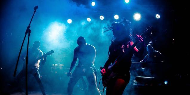 Retrato de la banda en plena actuación con una de las guitarristas en primer plano
