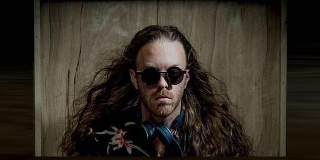 El DJ nord-americà retratat amb ulleres de sol rodones i uns cabells llargs que li cauen sobre les espatlles