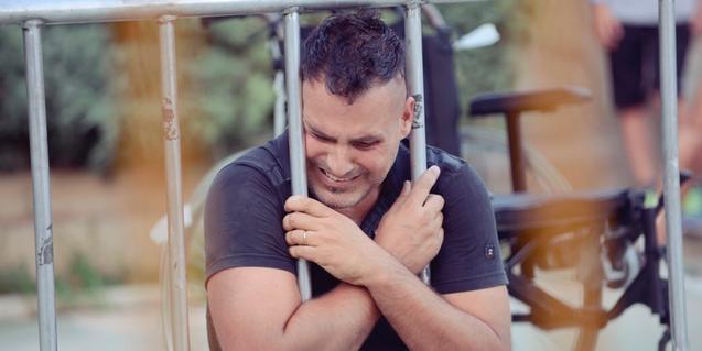 El artista Ferran Orobitg sujetando los barrotes de una valla metálica