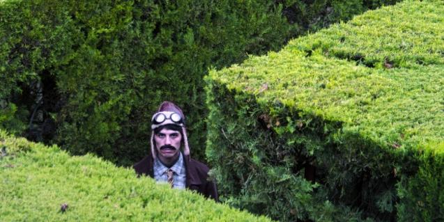 Un hombre con un casco de aviador perdido en un laberinto vegetal