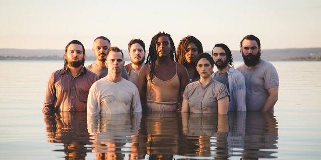 Liniker y los músicos de su banda retratados en un lago con el agua hasta la cintura