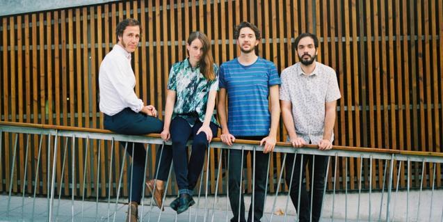 Els quatre integrants de la banda retratats mentre es recolzen en una barana