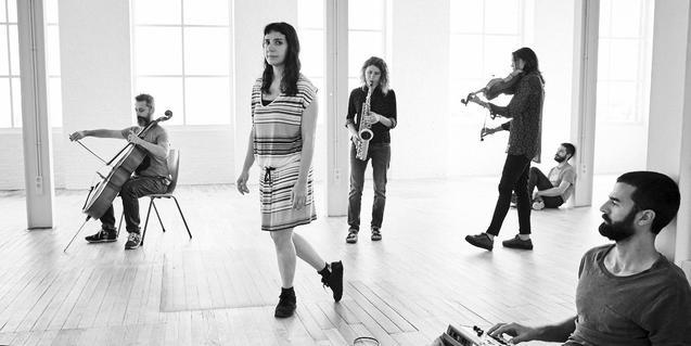 La cantante Laura Maure en una sala sin amueblar y rodeada de sus músicos