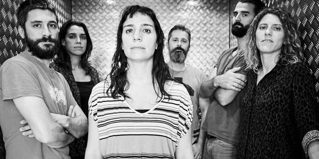 Retrato en blanco y negro de los seis músicos de la banda con Laura Maure en primer plano
