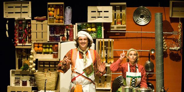 Escena de l'espectacle amb els dos protagonistes envoltats de menjar i estris de cuina