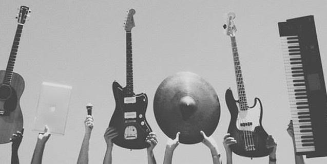 Unas manos sujetan unas guitarras, un teclado y un plato de batería