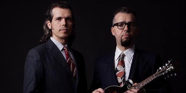 Els Hermanos Cubero, retratats amb americana i corbata sobre un fons negre i amb una mandolina a les mans