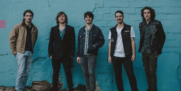Retrat dels cinc membres de la banda contra un mur del carrer