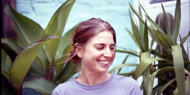 La artista rodeada de plantas y con el cabello en la cara