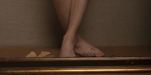 Uno de los retratos del artista muestra únicamente las piernas de la modelo encuadradas en un marco de madera