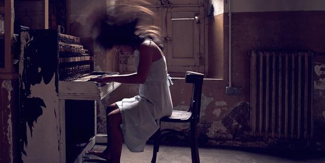 La artista tocando el piano mientras agita el cabello violentamente