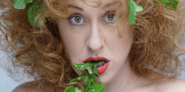 Retrato de la actriz protagonista mordisqueando una planta