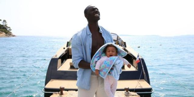 The daughter as a baby in her father's arms with the sea in the background.