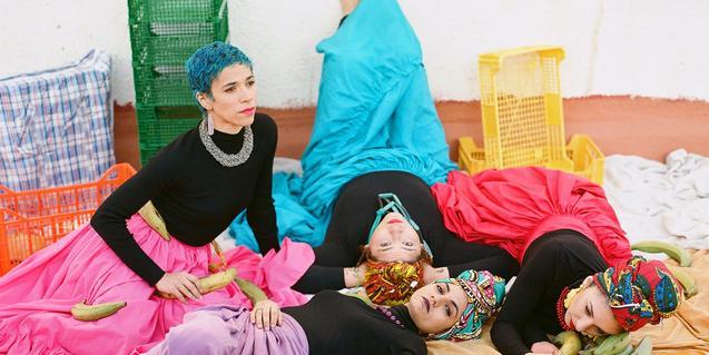 Les integrants de la formació vestides amb robes de colors i estirades pel terra