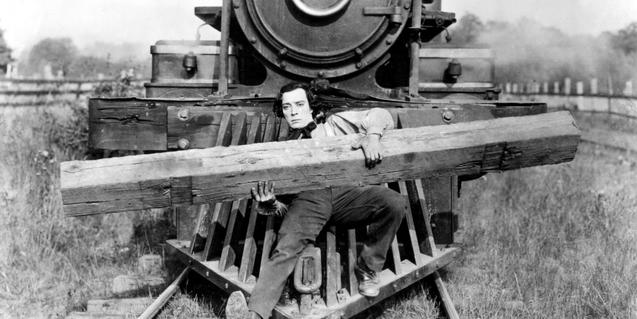 Fotograma de la película, Buster Keaton en la parte de delante del tren sosteniendo una vía de madera
