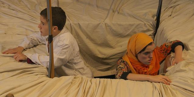 Un nen i una noia sortint d'un forat