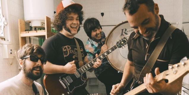 Los integrantes de la banda retratados mientras grababan un videoclip en el interior de un lavabo
