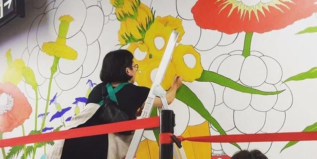 L'artista pujada a una escala i pintant la seva obra mural
