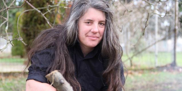 La guitarrista con el cabello largo y encanecido retratada en un bosque