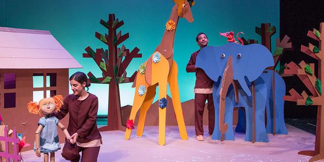 Fotografia de l'espectacle on s'hi veuen els dos actors movent titelles i animals de cartró.