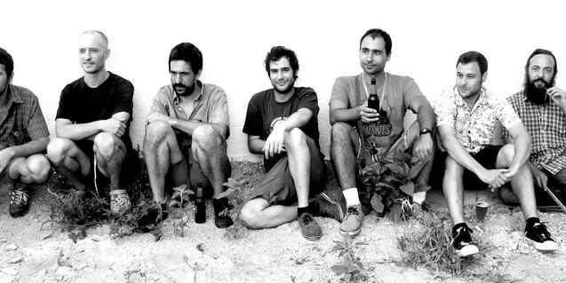 Los integrantes de la banda sentados en el suelo formando una fila