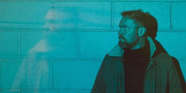 L'artista de folk rock retratat sota una llum blavosa contra una paret de maons