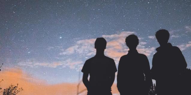 Imatge de tres persones contemplant el cel