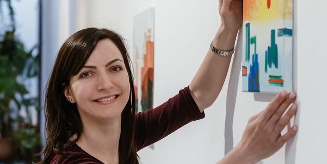 Retrato de la artista mostrando una de sus obras