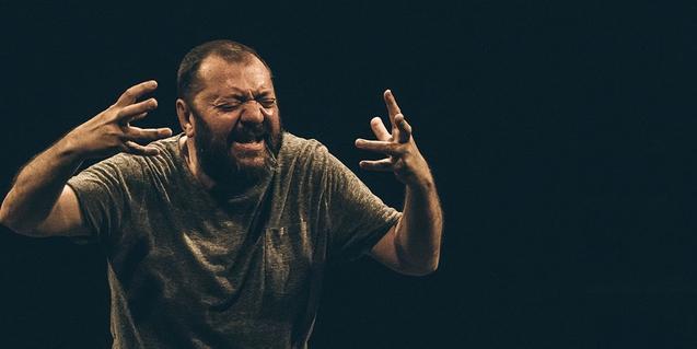 Uno de los actores de la compañía retratado gesticulando con las manos durante la actuación