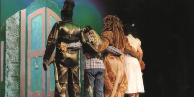 Fotografía de los cuatro protagonista en el escenario, de espaldas, a punto de abrir la puerta mágica.