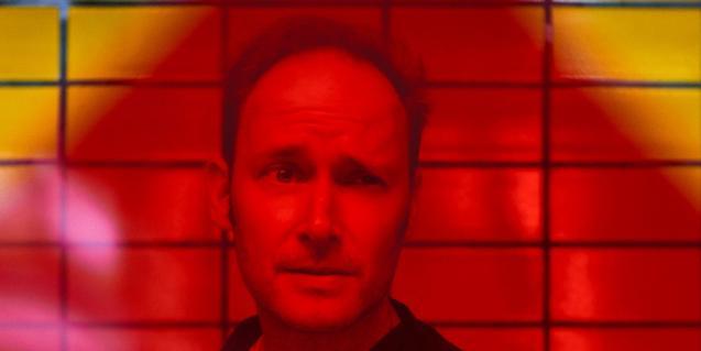 Una imagen del conocido DJ del sello Kompakt retratado en primer plano contra un fondo rojizo