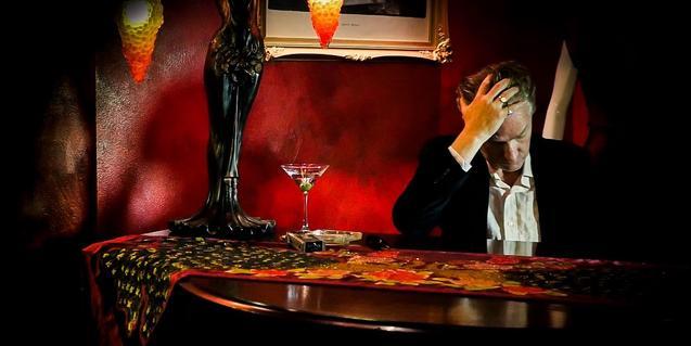 El músico australiano, sentado ante una mesa y bebiendose un cóctel