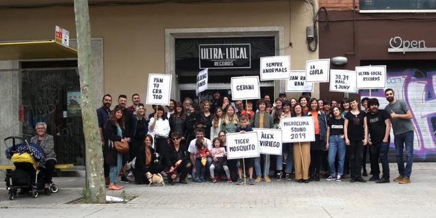 Un grupo de cerca de cuarenta personas ante la sede de Ultra-Local Records con carteles que anuncian los grupos participantes en el Microclima Sound de este año