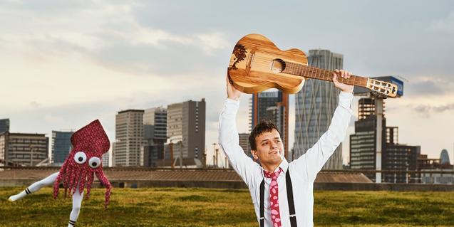 El artista rumbero Micu levanta su guitarra por encima de la cabeza en un paisaje urbano