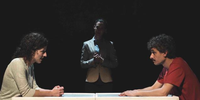 Dos personatges discuteixen asseguts en una taula mentre un mitjancer se'ls mira