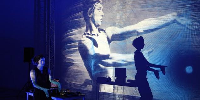 Un momento del espectáculo con una chica bailando y otra haciendo proyecciones sobre el muro