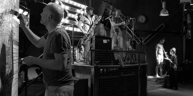 Unos músicos actúan mientras a ambos lados del escenario unos artistas plásticos pintan sus obras en una edición anterior del festival