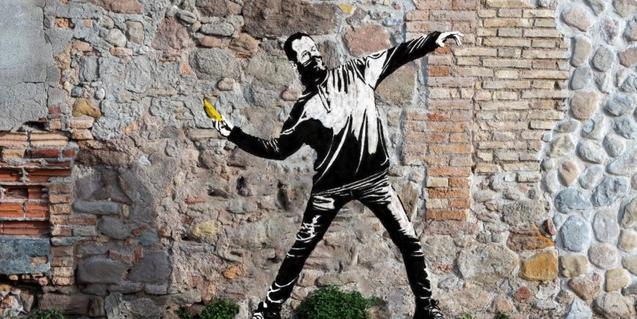 Una imatge en una paret d'un home emmascarat llançant un plàtan com si fos un còctel Molotov