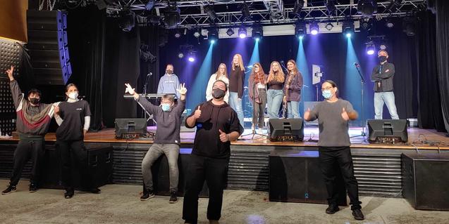 Els onze integrants de la formació amb mascaretes i fent el signe de la victòria amb els dits de la mà durant l'enregistrament d'una cançó