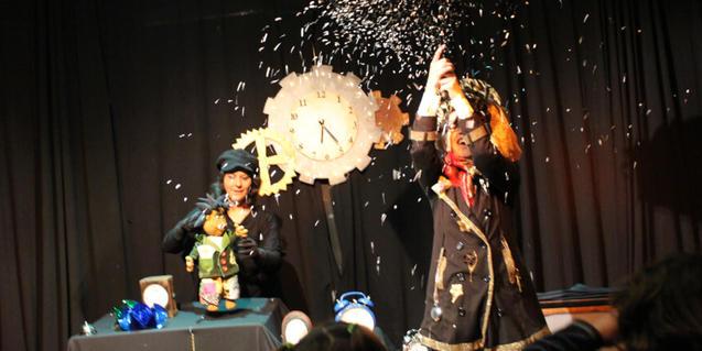 Fotografía del espectáculo. Las dos actrices en el escenario tirando confetti