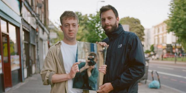 Els dos membres del duet retratats al carrer sostenint un mirall on es reflecteix el fotògraf