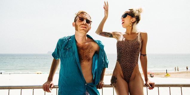 Los integrantes del dúo con gafas de sol y trajes de baño en la playa