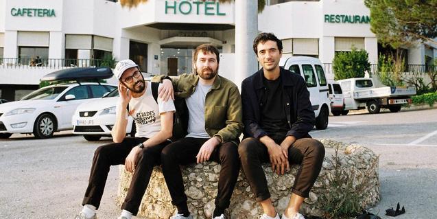 Los tres integrantes de la banda sentados en un banco ante un gran hotel